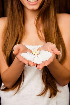 Close up Foto von langhaarigen Mädchen in Handtuch hält Orchidee Standard-Bild