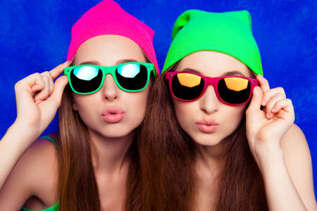 pouting: Portrait of two pretty sisters in hats and glasses pouting