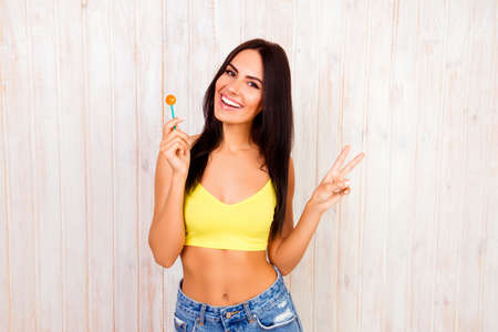 two fingers: Cheerful happy woman with lollipop gesturing with two fingers