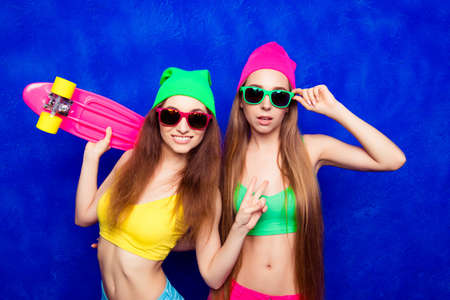lesbo: Young slim girls holding skateboard and gesturing with two fingers