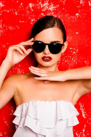 Portrait of stylish vogue woman in glasses on red background