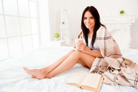 Beautiful romantic young woman with book basking with tea and blanket in bedroom Stock Photo