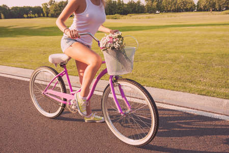 Close up photo of young woman riding cycle on the street Stock Photo