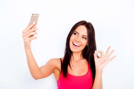 gesturing: Cheerful brunette gesturing OK and making selfie