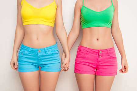 lesbo: Close up photo of two girls with slim bellies holding hands