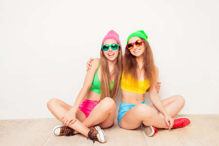 siting: Cheerful hipster sisters embracing while siting on floor