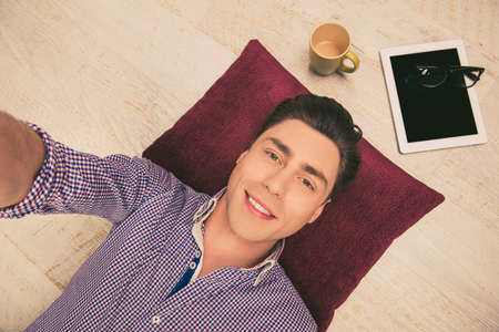 cadre: Selfie of handsome happy man lying on floor with tablet and cup of tea