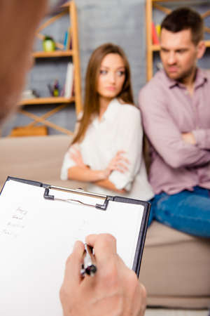 Young couple with problems. Focus on therapist folder Stock Photo