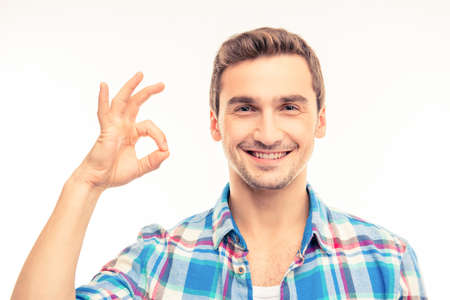 express positivity: Portrait of a cute handsome young man gesturing ok