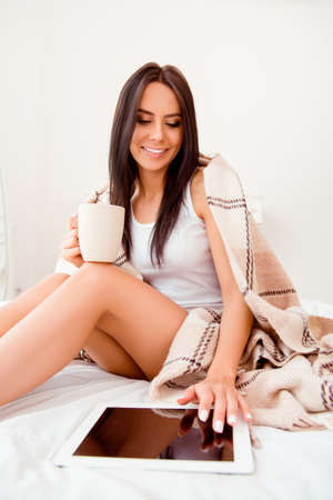 Portrait of cute woman in plaid with cup of tea touching screen of tablet