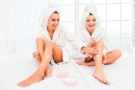 bathrobes: Attractive sensual women in bathrobes applying cream on their legs Stock Photo