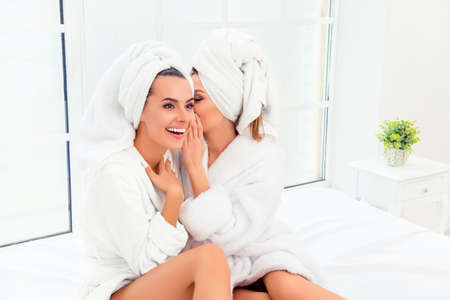 bathrobes: Portrait of two happy gossips in bathrobes having private talk Stock Photo