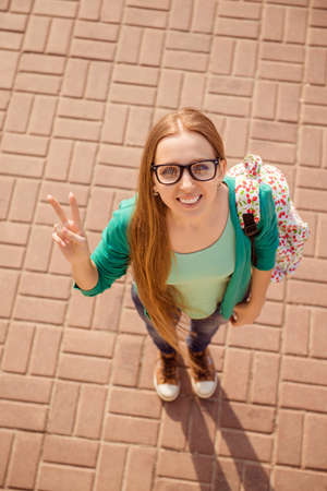 fingers on top: Top view of happy smiling woman in glasses showing two fingers