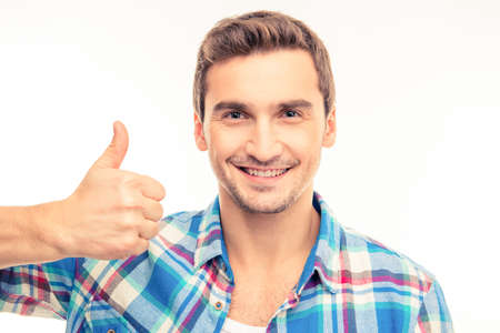 express positivity: Portrait of a cute handsome young man showing thumb up