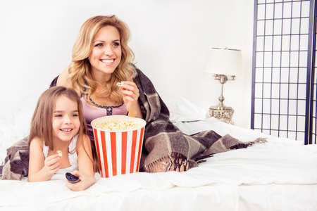 Happy cheerful family sitting on bed with popcorn and watching video Stock Photo