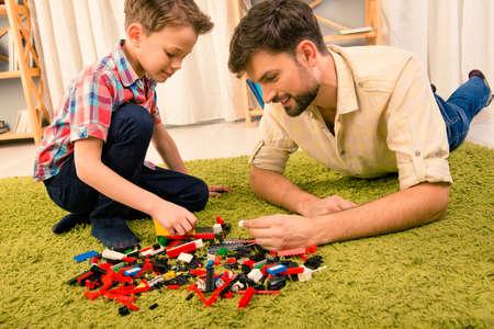 여가 시간. 흥분된 아버지와 아들이 생성자와 놀고 스톡 콘텐츠