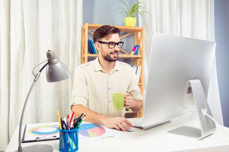 trabajando duro: Handsome businessman working hard and drinking coffee