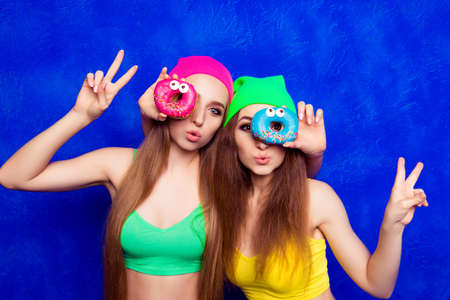 lesbo: Beautiful young women holding color donutes near eyes