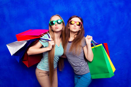 pouting: Pretty stylish girls in glasses holding packs and pouting Stock Photo