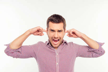 spite: Attractive man clossing his ears and screaming Stock Photo