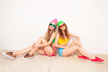siting: Two happy girls in caps and glasses siting on floor Stock Photo