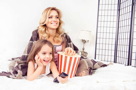 Young mother and her happy child watching tv with popcorn Stock Photo