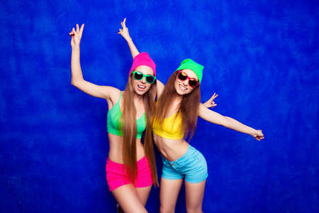 lesbo: Two trendy women in hats and spectacles dancing on blue background Stock Photo