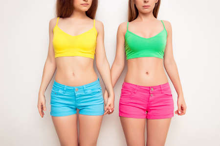 sexy gay: Portrait of two slim sexy women demonstrating their bellies Stock Photo