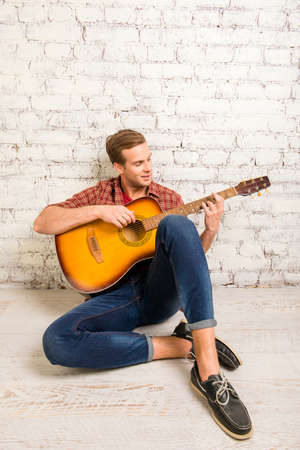 siting: Handsome man  siting on floor and playing on the guitar