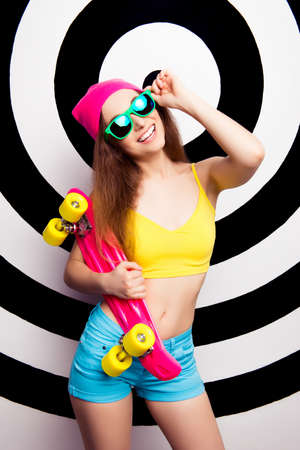 teeny: Happy girl in spectacles holding skate and showing her slim belly Stock Photo