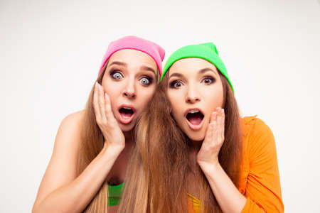wonderment: Two surprised girls with open mouth touching their faces
