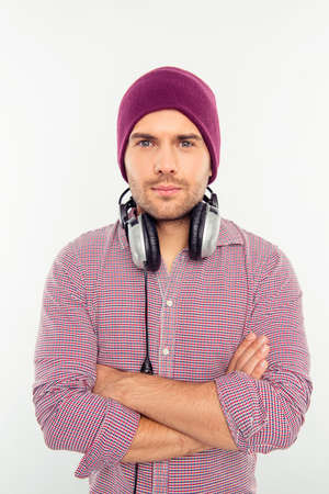 Serious man in hat and headphones with crossed hands