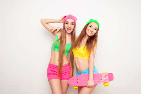 bisexual women: Two beautiful and young girlfriends having fun with a skateboard Stock Photo