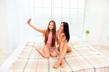 lesbo: Sexy attractive girls in pajamas making selfie in bedroom