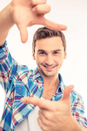 express positivity: Young handsome man gesturing finger frame