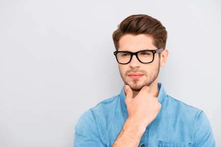 Young calm guy in glasses dreaming and touching chin Stock Photo