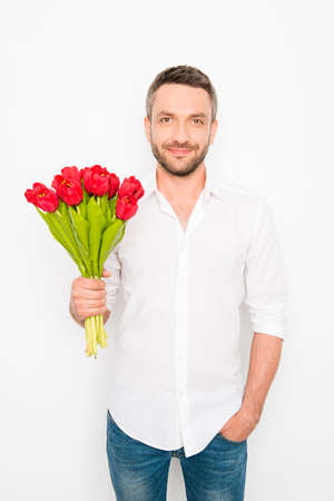 Portrait of handsome happy man holding bouquet of tulips