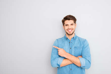 Happy handsome guy showing way and pointing with finger Stock Photo - 61229747