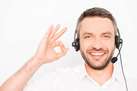 caller: Happy smiling man in head-phones gesturing OK Stock Photo