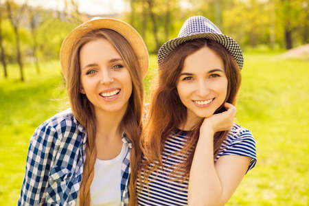 lesbo: Portrait of two positive smiling girls in caps walking in the park Stock Photo