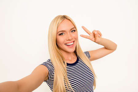 two fingers: Blonde happy woman making selfie and showing two fingers