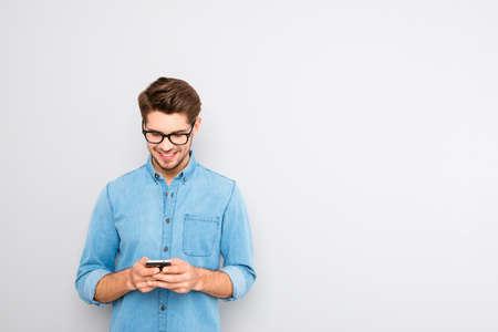 Szczęśliwy mężczyzna pisać na maszynie sms w szkłach na popielatym tle