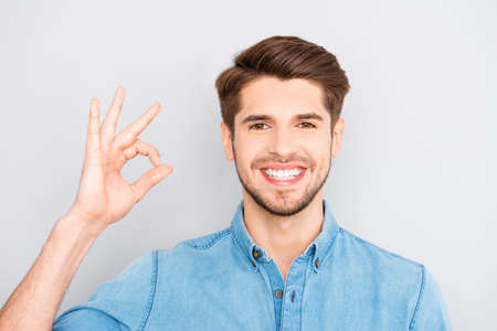 Cheerful young successful toothy businessman gesturing OK