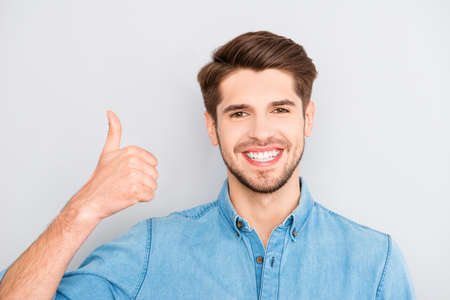 Happy man with beaming smile showing thumb up Stock Photo