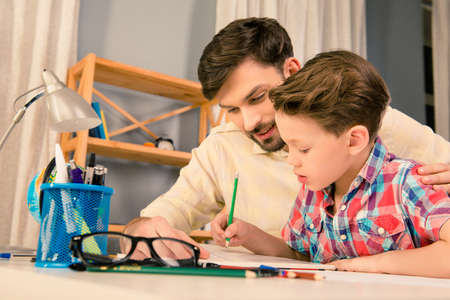 Happy family. Father and son doing homework together Reklamní fotografie