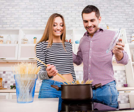 Happy young couple in love  boiling  pasta in the kitchen