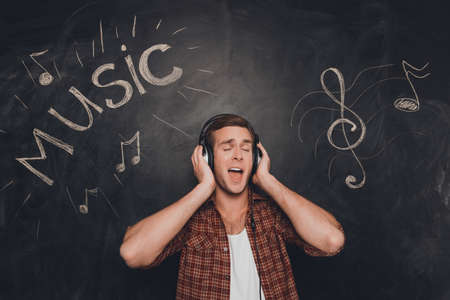 handsome young man: Handsome young man in head-phones listening music and singing