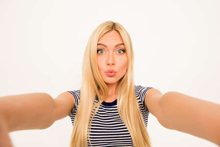 Pretty young blonde woman making selfie and pouting
