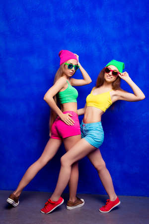lesbo: Pretty cool hipster women posing in caps and glasses Stock Photo