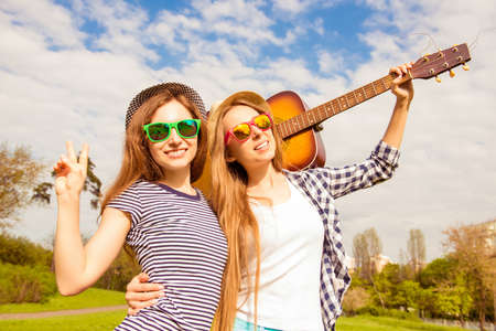 instrumentalist: Portrait of beautiful women in glasses holding guitar in the park